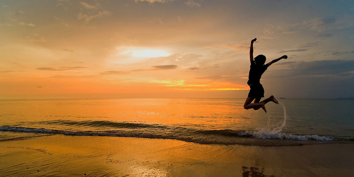 A Panorama of a Woman Jumping for Joy on the Beach at Sunset